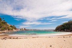 Abgelegener Strand mit grünem Wasser und blauem Himmel Stockbild
