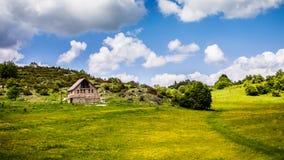 Abgelegenes Haus in der Mitte des grünen Gebirgstales lizenzfreies stockbild