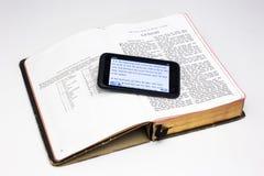 Abgenutzte Bibel und Smartphone - Entstehungsgeschichte Stockfotografie