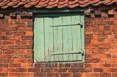 Abgenutzte kleine Holztür eingestellt in alte Ziegelsteine Stockbilder