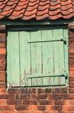 Abgenutzte kleine Holztür eingestellt in alte Ziegelsteine Stockfotografie