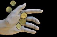 Abgenutzte Puppehand, die Euromünzen anhält lizenzfreies stockfoto