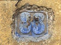83 in abgenutzten Buchstaben auf Wand Stockfoto
