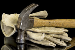 Abgenutzter Hammer und alte Handschuhe Stockfoto