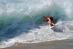 Abgeschöpft-Internatsschüler, der eine Uferbruchwelle an Aliso-Strand im Laguna Beach, Kalifornien reitet Stockfotografie