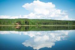 Abgeschlossene Kabine auf einem reflektierenden See in Yukon, Kanada lizenzfreie stockfotos