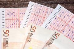 Abgeschlossene Lottoscheine mit Bargeld als Symbol der Kosten oder des Lotteriepreises stockfotografie