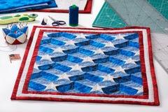 Abgeschlossene Steppdecke mit stilisierten Elementen der amerikanischer Flagge, Patchworkwerkzeuge Lizenzfreie Stockfotos