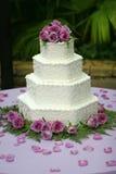 Abgestufter Hochzeits-Kuchen mit purpurroten Blumen Stockbild