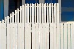 Abgestufter weißer Zaun des Pfostens zwei vor einem blauen Gebäude Lizenzfreies Stockbild
