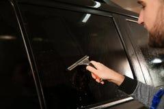 Abgetöntes Autofenster der Arbeitskraft Reinigung im Geschäft lizenzfreies stockbild
