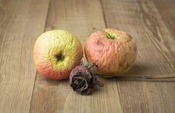 Abgetragener Apfel und rosafarbenes Stillleben auf hölzernem Hintergrund Lizenzfreie Stockfotografie