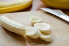 Abgezogene Banane geschnitten auf Schneidebrett mit einem Messer Lizenzfreie Stockfotografie
