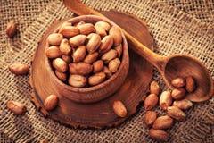 Abgezogene Erdnüsse in einer hölzernen Schüssel auf einer alten Leinwand Lizenzfreies Stockfoto