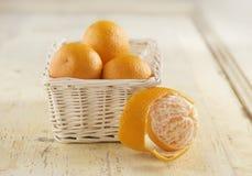 Abgezogene Mandarine vor Korb von Orangen Lizenzfreies Stockfoto