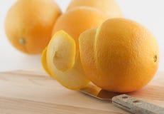 Abgezogene Orange und Messer Stockfotografie