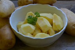 Abgezogene potatos mit Petersilie in der weißen Schüssel auf hölzernem Hintergrund Lizenzfreies Stockfoto