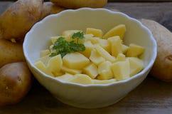 Abgezogene potatos mit Petersilie in der weißen Schüssel auf hölzernem Hintergrund Lizenzfreie Stockfotografie