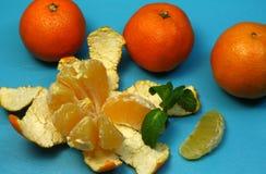 Abgezogene reife Tangerine auf einem blauen Hintergrund mit orange Tangerine und Minze Stockfotos
