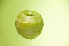 Abgezogener Apfel auf grünem Hintergrund Lizenzfreie Stockfotografie