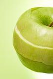 Abgezogener Apfel auf grünem Hintergrund Stockfotografie