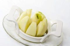Abgezogener grüner Apfel in einer Apfelschneidmaschine Stockfotografie