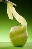 Abgezogener grüner Apfel und Schäler Stockfotografie
