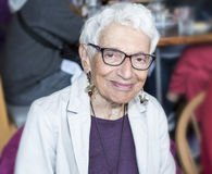 Abhängige ältere Frau bei Restauarant lächelnd u. glücklich Lizenzfreie Stockbilder