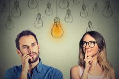 Abilità conoscitive maschii contro la femmina Uomo e donna che esaminano lampadina Immagini Stock