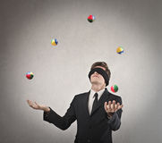 Ability. Young businessman blindfolded playing with balls Royalty Free Stock Photography