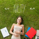 Ability against pretty student lying on grass Royalty Free Stock Photos