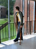 Ability Limited. College student stands on crutches in college dormatory staring out the window.  He is struggling to make classes with his disability Royalty Free Stock Photos