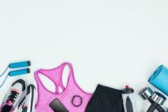 Abiti sportivi con le scarpe da tennis, lo smartphone, l'inseguitore di forma fisica e l'attrezzatura di forma fisica Fotografia Stock