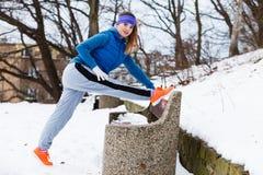 Abiti sportivi d'uso della donna che si esercitano fuori durante l'inverno Immagini Stock Libere da Diritti