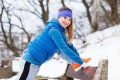 Abiti sportivi d'uso della donna che si esercitano fuori durante l'inverno Immagini Stock