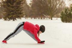 Abiti sportivi d'uso della donna che si esercitano fuori durante l'inverno Fotografie Stock