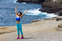 Abiti sportivi d'uso della giovane donna che si esercitano sulla spiaggia Fotografia Stock Libera da Diritti