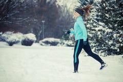 Abiti sportivi d'uso della ragazza corrente, forma fisica di inverno Immagini Stock