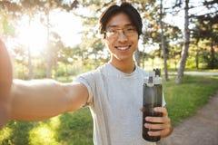 Abiti sportivi d'uso sorridenti dell'uomo asiatico dell'atleta immagini stock