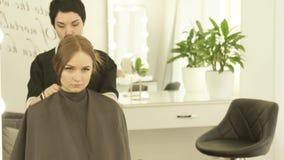 Abito d'uso del cloack del parrucchiere sulla giovane donna prima di taglio di capelli nello studio dei capelli Preparando per il stock footage