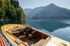 Beautiful rarity wooden speed boat on the background of the mountains on Lake Ritsa. ABKHAZIA, GEORGIA, 17 SEPTEMBER 2017: Beautiful rarity wooden speed boat on Royalty Free Stock Photos