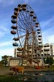 Abkhazia, rusty destroy ferris wheel. Abkhazia, Ochamchira city. Rusty destroy ferris wheel and war-ravaged spa-hotel background after georgia-abkhazian war 1992 Stock Image