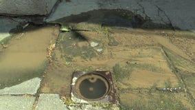 Ablassen des Wassers aus der Wasserleitung, die hinunter den Bürgersteig des Dorfs, gebrochene Armatur fließt stock footage