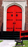 Ablaze. Old church as fire engine red door. Park bench sits in front of the old brick building stock photo