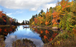 Ablaze with Color in Michigan. Autumn is reflected in still waters on the Keweenaw Peninsula in Michigan.  Water is tinted with orange and yellow in a blaze of Stock Image