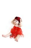 Ablaze in Red. Adorable infant sits in a red tutu and doffs a red tam in red check with black bow.  She is wearing a string of red beads and a bracelet lays at Royalty Free Stock Photo
