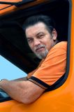 Able and Experienced. Big truck driver leans out of cab. Uniform and truck is orange royalty free stock images