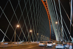 Сable-stayed through arch bridge over river Ob in Novosibirsk at night, Siberia. People and cars were on the bridge in the day when it was opened. Red cable Royalty Free Stock Photos
