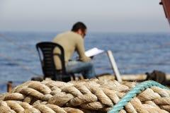 Ablesen eines Buches auf dem Dock Stockfoto