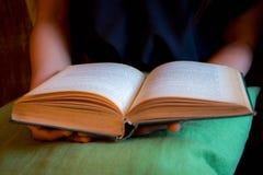 Ablesen eines Buches und des Buches in Mädchen ` s Händen Stockfotografie
